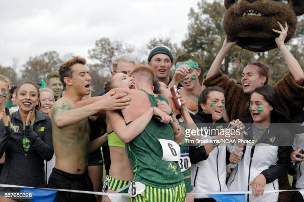 Dalton Grahm of Adams State University is hugged by teammates during the Division II Men's Cross Country Championship held at the Angel Mounds on...