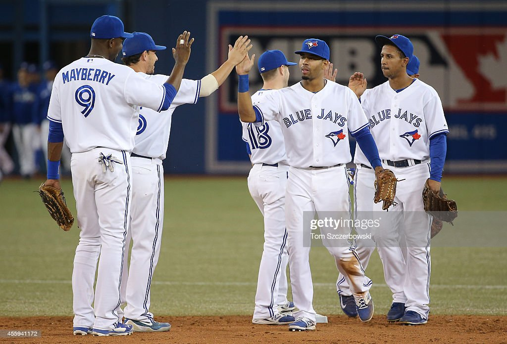 Dalton Pompey #45 and Danny Valencia #15 of the Toronto Blue Jays celebrate with teammates after a win against the Seattle Mariners on September 22, 2014 at Rogers Centre in Toronto, Ontario, Canada.