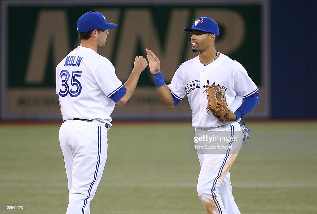 Dalton Pompey #45 and Sean Nolin #35 of the Toronto Blue Jays celebrate a victory over the Seattle Mariners on September 22, 2014 at Rogers Centre in Toronto, Ontario, Canada.
