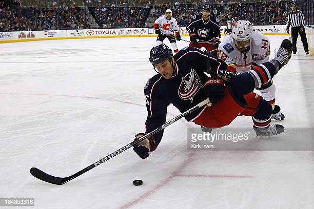 Dalton Prout of the Columbus Blue Jackets looses his footing while battling for a loose puck with Jarome Iginla of the Calgary Flames during the...
