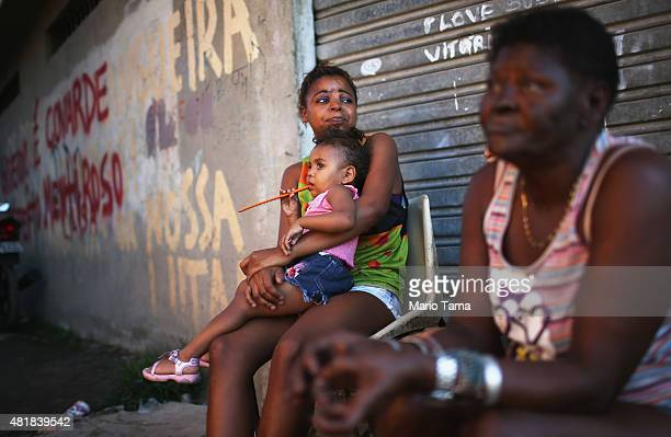 Dalva Martins sits with Thalia Martins holding Ana Clara near the rubble of destroyed homes in the MetroMangueira community or 'favela' located...