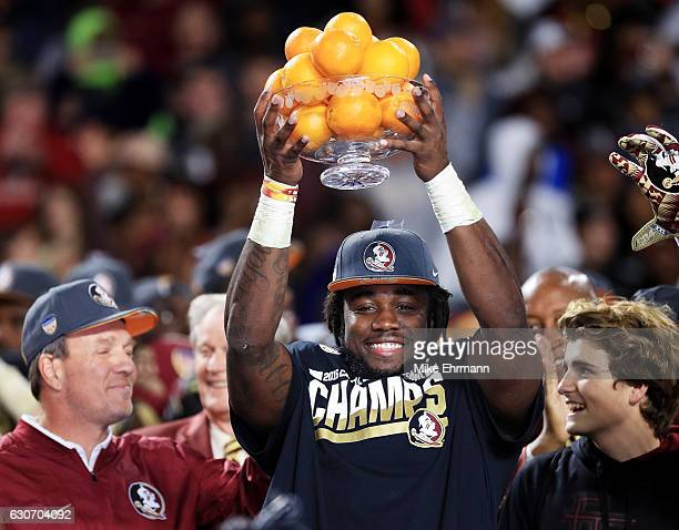 Dalvin Cook and head coach Jimbo Fisher of the Florida State Seminoles celebrate their 33 to 32 win over the Michigan Wolverines during the Capitol...