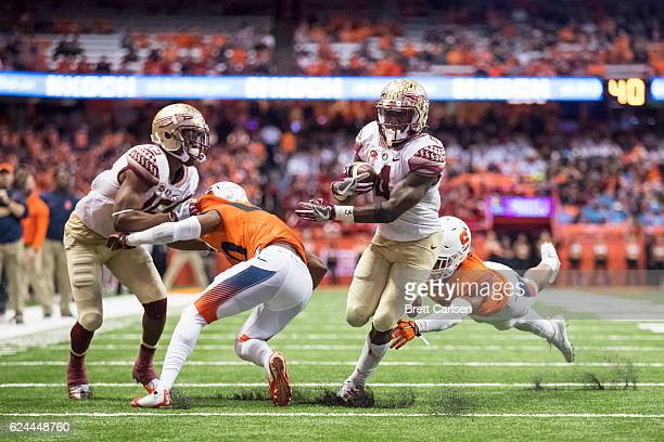 Dalvin Cook of the Florida State Seminoles breaks a tackle to run in his final touchdown of the day against the Syracuse Orange during the third...