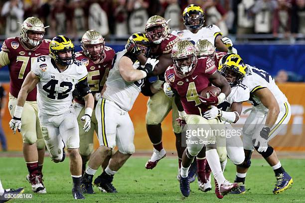 Dalvin Cook of the Florida State Seminoles carries the ball against the Michigan Wolverines during the Capitol One Orange Bowl at Sun Life Stadium on...