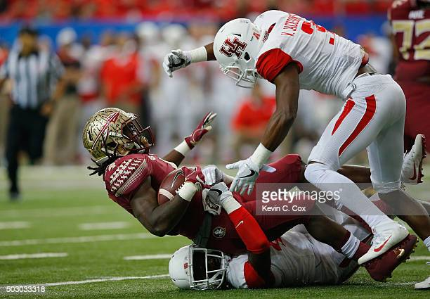 Dalvin Cook of the Florida State Seminoles is tackled by Steven Taylor and William Jackson III of the Houston Cougars in the first quarter during the...
