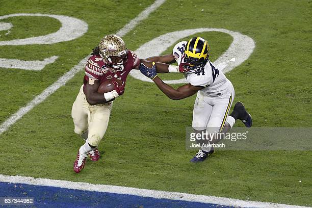 Dalvin Cook of the Florida State Seminoles runs past the attempted tackle by Delano Hill of the Michigan Wolverines during the 2016 Capital One...