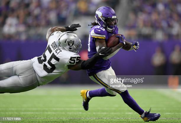 Dalvin Cook of the Minnesota Vikings avoids a tackle by Vontaze Burfict of the Oakland Raiders during the second quarter of the game at U.S. Bank...