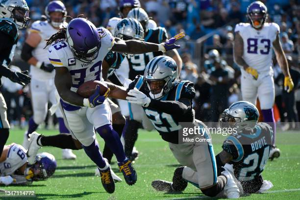 Dalvin Cook of the Minnesota Vikings avoids the tackle from Jeremy Chinn of the Carolina Panthers for a touchdown during the third quarter at Bank of...