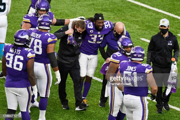 Dalvin Cook of the Minnesota Vikings is helped by training staff after suffering an injury during the third quarter against the Carolina Panthers at...