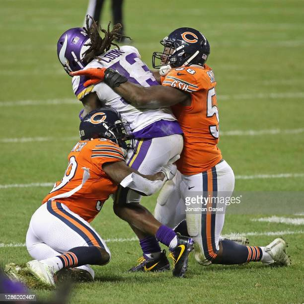 Dalvin Cook of the Minnesota Vikings is tackled by Eddie Jackson and Roquan Smith of the Chicago Bears at Soldier Field on November 16, 2020 in...