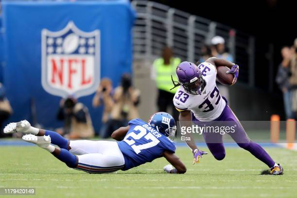 Dalvin Cook of the Minnesota Vikings runs the ball against Deandre Baker of the New York Giants during the first half in the game at MetLife Stadium...