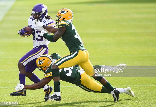 Dalvin Cook of the Minnesota Vikings runs the ball as Adrian Amos of the Green Bay Packers and Josh Jackson of the Green Bay Packers defend during...
