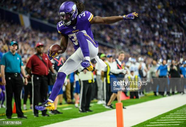 Dalvin Cook of the Minnesota Vikings runs with the ball and leaps over the goal line for a touchdown in the second quarter of the game against the...