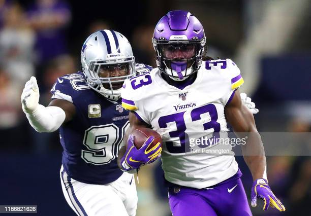 Dalvin Cook of the Minnesota Vikings runs with the ball as he is pursued by DeMarcus Lawrence of the Dallas Cowboys during the first half at AT&T...