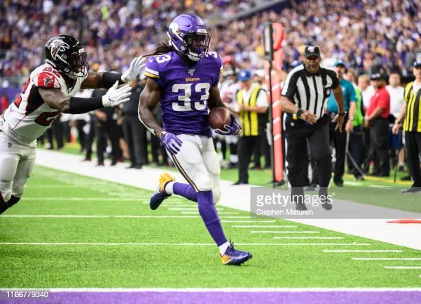 Dalvin Cook of the Minnesota Vikings runs with the ball for a touchdown as Keanu Neal of the Atlanta Falcons runs defense in the first quarter of the...