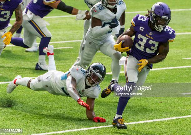 Dalvin Cook of the Minnesota Vikings runs with the ball for a touchdown in the first quarter of the game against the Tennessee Titans at U.S. Bank...