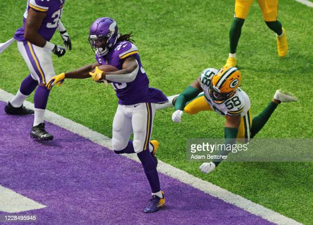 Dalvin Cook of the Minnesota Vikings scores a touchdown against Christian Kirksey of the Green Bay Packers in the first quarter at U.S. Bank Stadium...