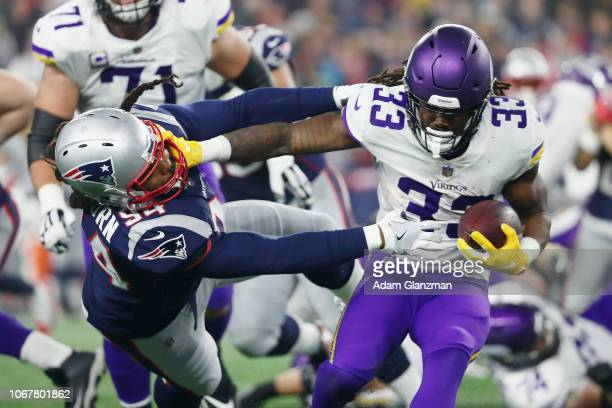 Dalvin Cook of the Minnesota Vikings stiff arms Adrian Clayborn of the New England Patriots during the second half at Gillette Stadium on December 2,...