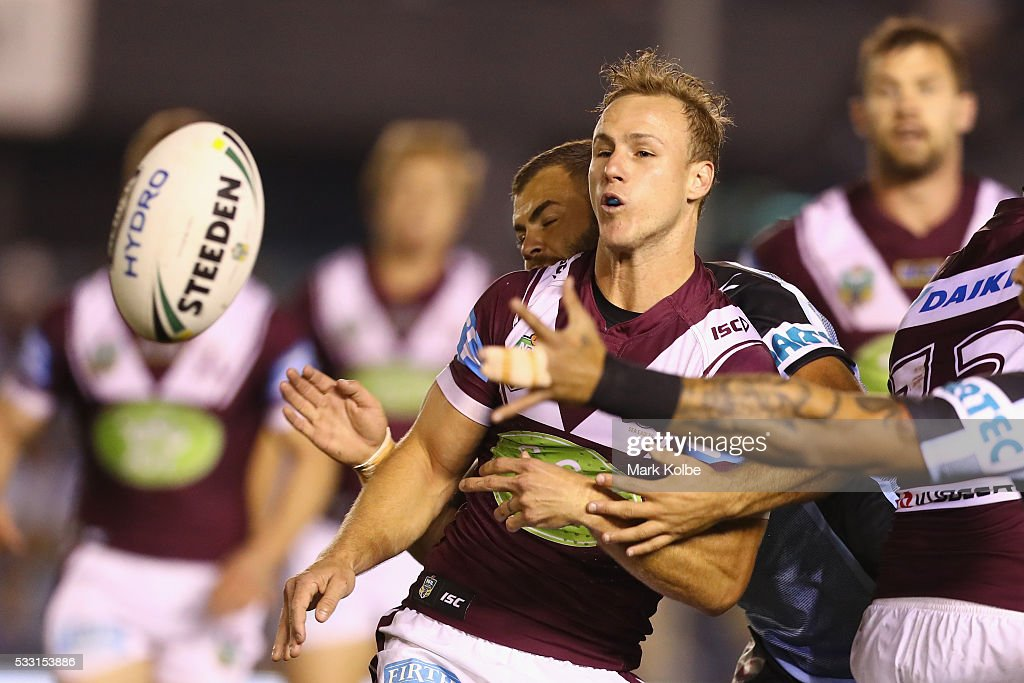 Daly Cherry-Evans of the Eagles passes as he is tackled by Wade Graham of the Sharks during the round 11 NRL match between the Cronulla Sharks and the Manly Sea Eagles at Southern Cross Group Stadium on May 21, 2016 in Sydney, Australia.