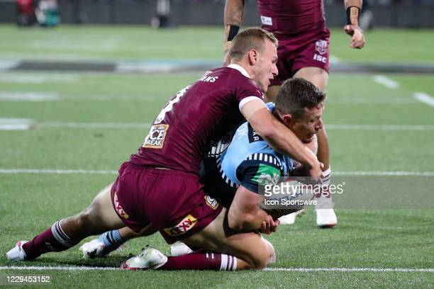 Daly Cherry-Evans of the QLD Maroons tackles Damien Cook of the NSW Blues during game one of the 2020 State of Origin series between the Queensland...