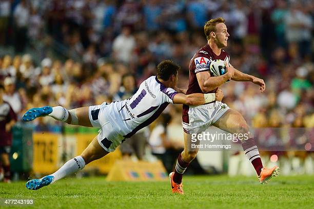 Daly Cherry-Evans of the Sea Eagles breaks free from a tackle by Billy Slater of the Storm during the round one NRL match between the Manly Sea...