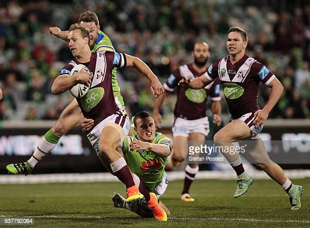 Daly CherryEvans of the Sea Eagles is tackled during the round 13 NRL match between the Canberra Raiders and the Manly Sea Eagles at GIO Stadium on...