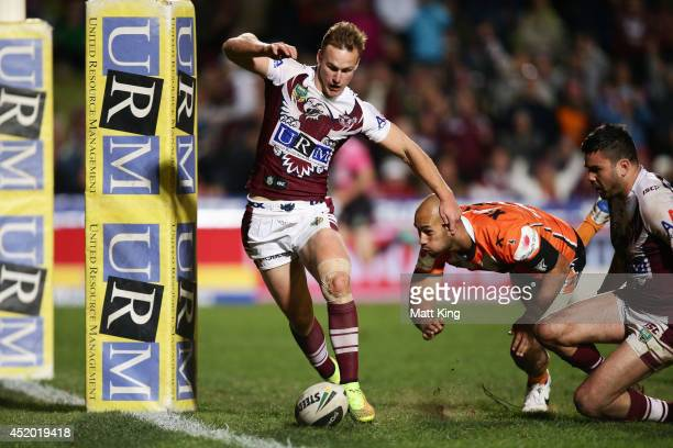 Daly Cherry-Evans of the Sea Eagles kicks the ball along the ground to score a try during the round 18 NRL match between the Manly Warringah Sea...