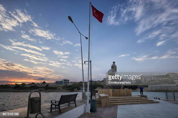 dalyankoy marina entrance with a fisherman and the statue of admiral turgut reis,cesme. - emreturanphoto stock pictures, royalty-free photos & images
