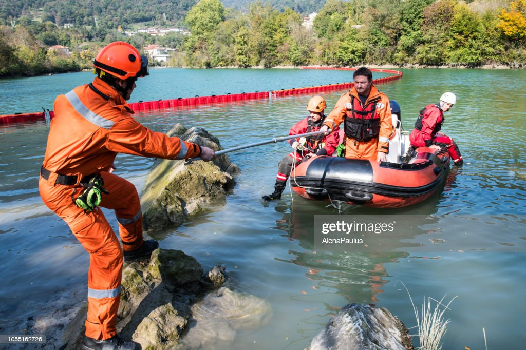 Dam construction on the river - rescue operation with a boat, oil spill : Stock Photo