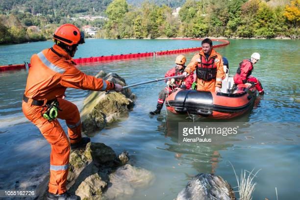dam construction on the river - rescue operation with a boat, oil spill - flooding stock photos and pictures