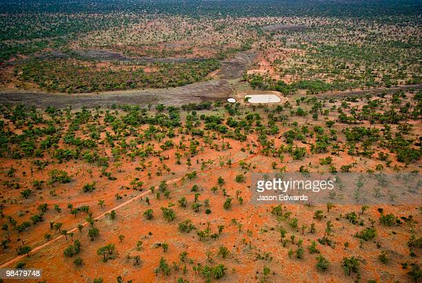 A dam waters cattle on a remote outback station in the red desert.