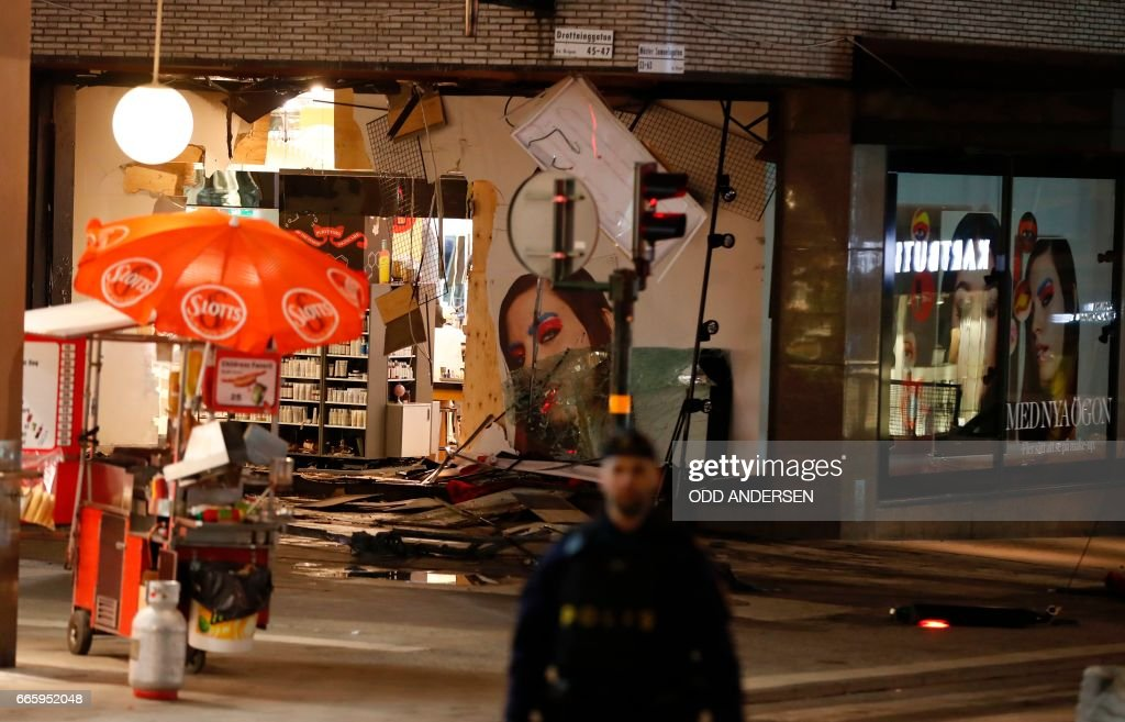 TOPSHOT - Damage to a store is revealed after the stolen truck, which was driven through a crowd outside a department in Stockholm on April 7, 2017, was taken away on April 8. A massive manhunt was underway for the driver of the stolen truck that ploughed into the crowd, killing four and injuring 15, Swedish police said. National police chief, Stefan Hector, said the police's 'working hypothesis is that this is a terror attack.' / AFP PHOTO / Odd ANDERSEN