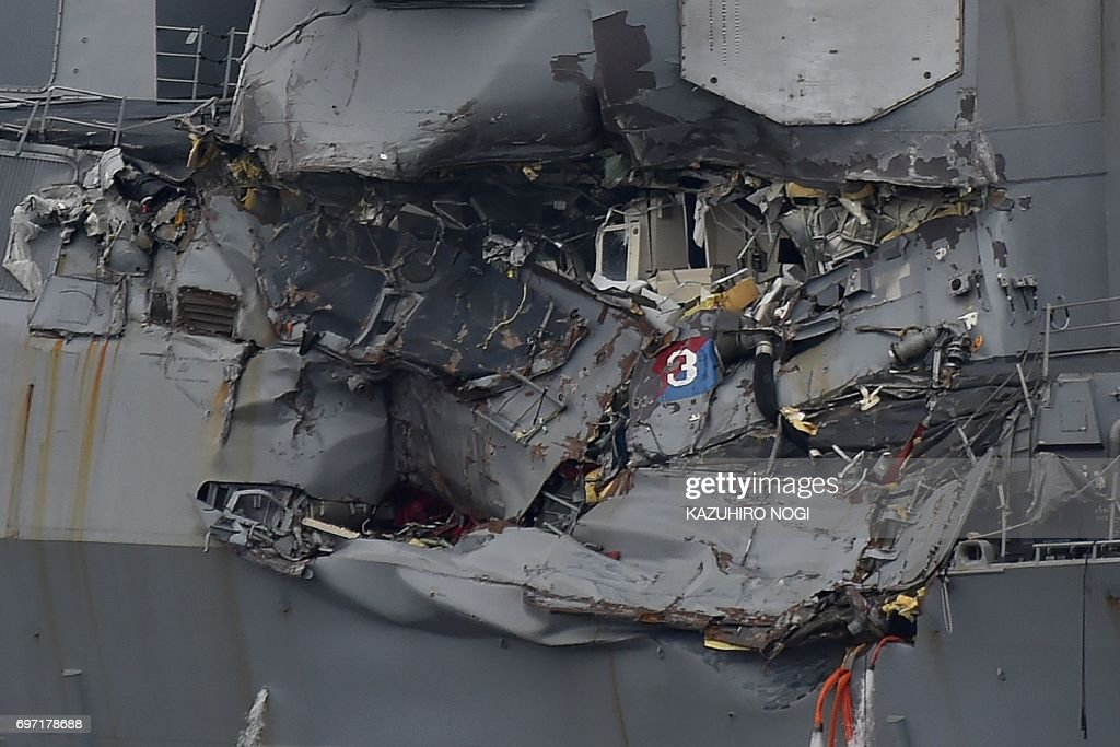 Damage to the guided missile destroyer USS Fitzgerald is seen as the vessel is berthed at its mother port in Yokosuka, southwest of Tokyo, on June 18, 2017. The bodies of US sailors missing after their destroyer collided with a container ship off Japan have been found in flooded sleeping berths, a day after the accident tore a huge gash in the warship's side, the US Navy said on June 18. / AFP PHOTO / Kazuhiro NOGI