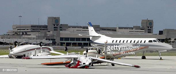 Damaged air planes lie on the tarmac of Palm Beach International Airport 26 September 2004 as Hurricane Jeanne battered Florida smashing homes...
