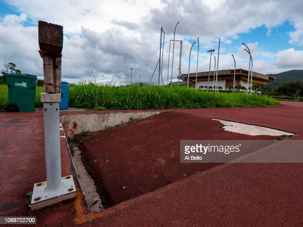A damaged athletics track overun by uncut grass is shown along with the damaged steeplechase jump discus area and athletics building caused by...