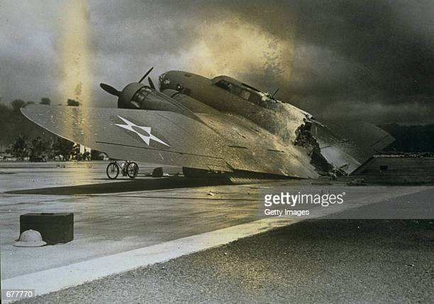 A damaged B17C bomber sits on the tarmac near Hangar Number 5 at Hickam Field December 7 1941 after the Japanese attack on Pearl Harbor Hawaii...