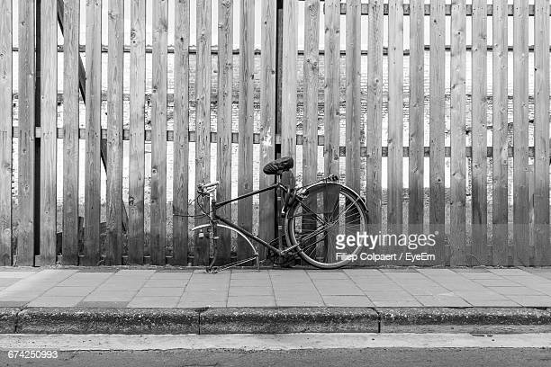 Damaged Bicycle Leaning On Wooden Fence