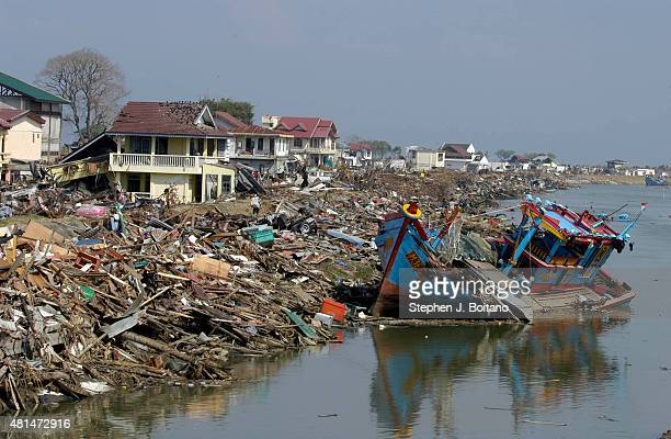 A damaged boat rests next to shore on the Sangai Kreung Aceh River in Banda Aceh Indonesia 150 miles from southern Asia's massive earthquake's...