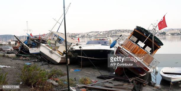 Damaged boats are seen on a beach following a sea surge caused by an earthquake on July 21 2017 in Bodrum southwestern Turkey Two foreigners died and...