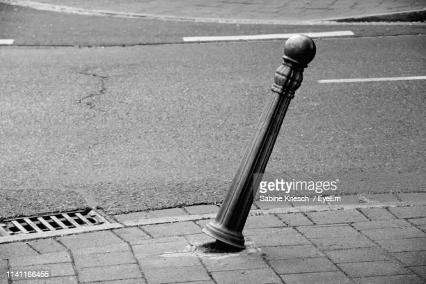 damaged bollard on sidewalk in city - sabine kriesch stock-fotos und bilder