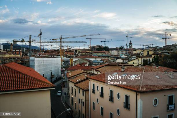 damaged building and cranes in l'aquila in the morning - l'aquila foto e immagini stock