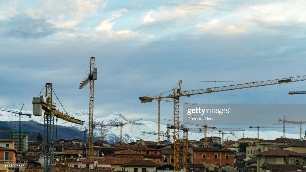 Damaged building and cranes in L'Aquila in the morning : ストックフォト