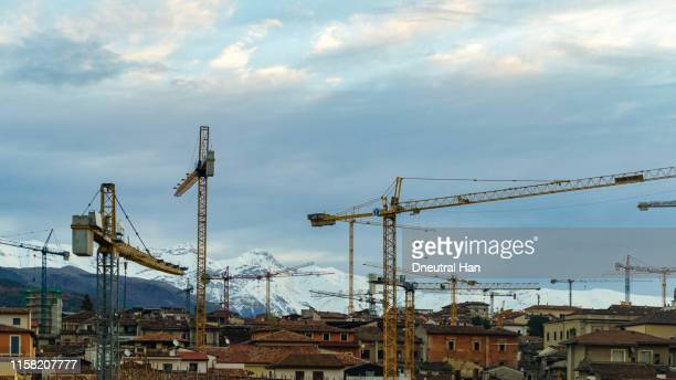 damaged building and cranes in l'aquila in the morning - l'aquila stock pictures, royalty-free photos & images