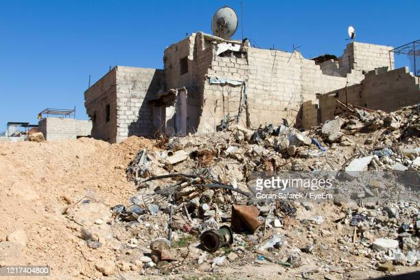 damaged building in syria against clear blue sky - war stock pictures, royalty-free photos & images