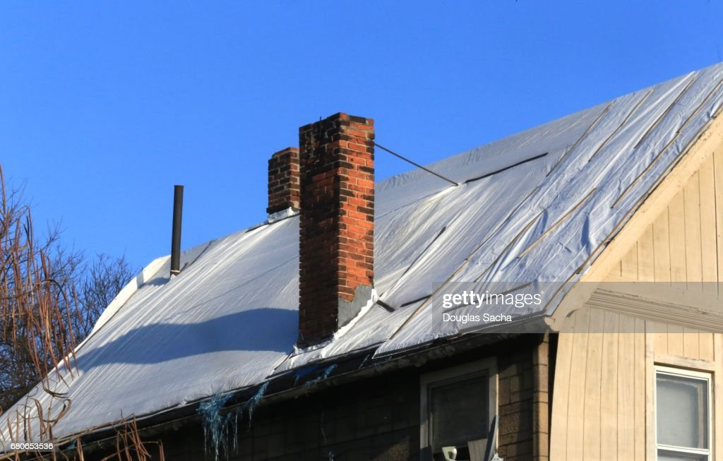 damaged building roof covered in plastic tarp stock photo
