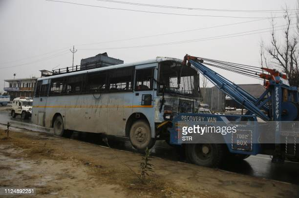 A damaged bus is towed away following an attack on a paramilitary Central Reserve Police Force convoy that killed at least 16 troopers and injured...