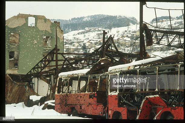 Damaged buses and buildings sit March 5, 1996 in Sarajevo, Bosnia-Herzegovina. The city is reopening its businesses, repairing damages from the war,...