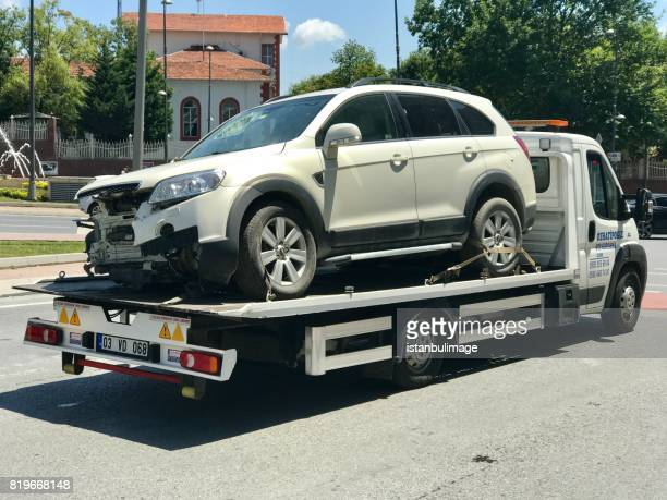 damaged car after accident on tow truck - tow truck stock photos and pictures