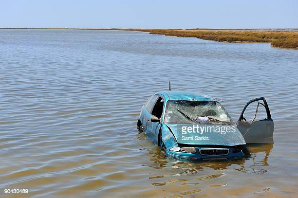 Damaged car half flooded in water