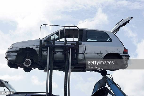 A damaged car is lifted at Allo Casse Auto's car demolition site in Athis Mons France on Wednesday Feb 24 2010 French consumer spending declined in...